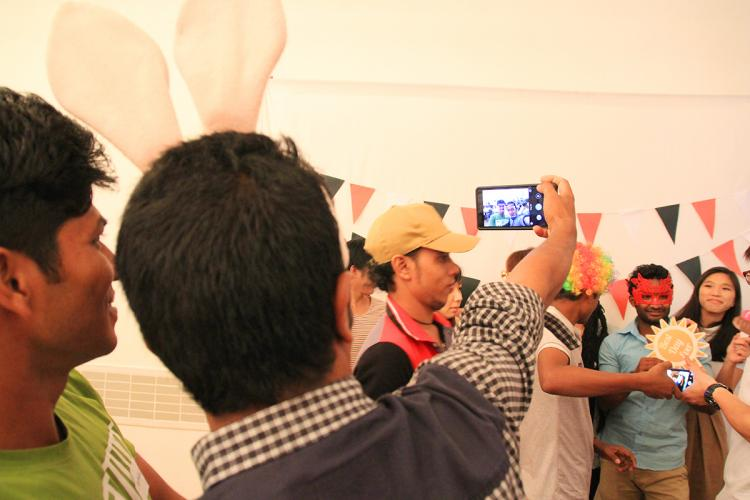 Two migrant workers take a selfie together at the fun and well-attended event. PHOTO: LU YAWEN