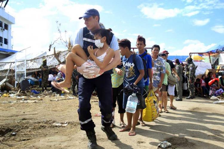 A rescue worker carried a victim and led evacuees to military aircrafts bound for Manila and Cebu. PHOTO COURTESY OF KEVIN LIM/ The Straits Times